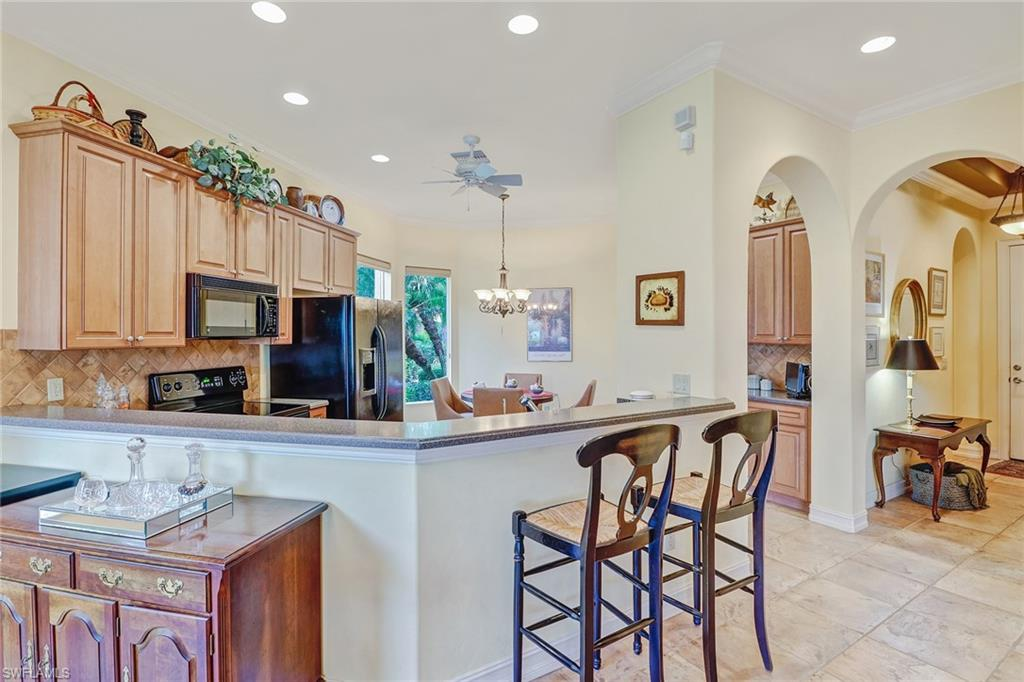 breakfast bar, eat in kitchen, wood upgraded cabinets with 2014 GE black appliances, corian counter tops